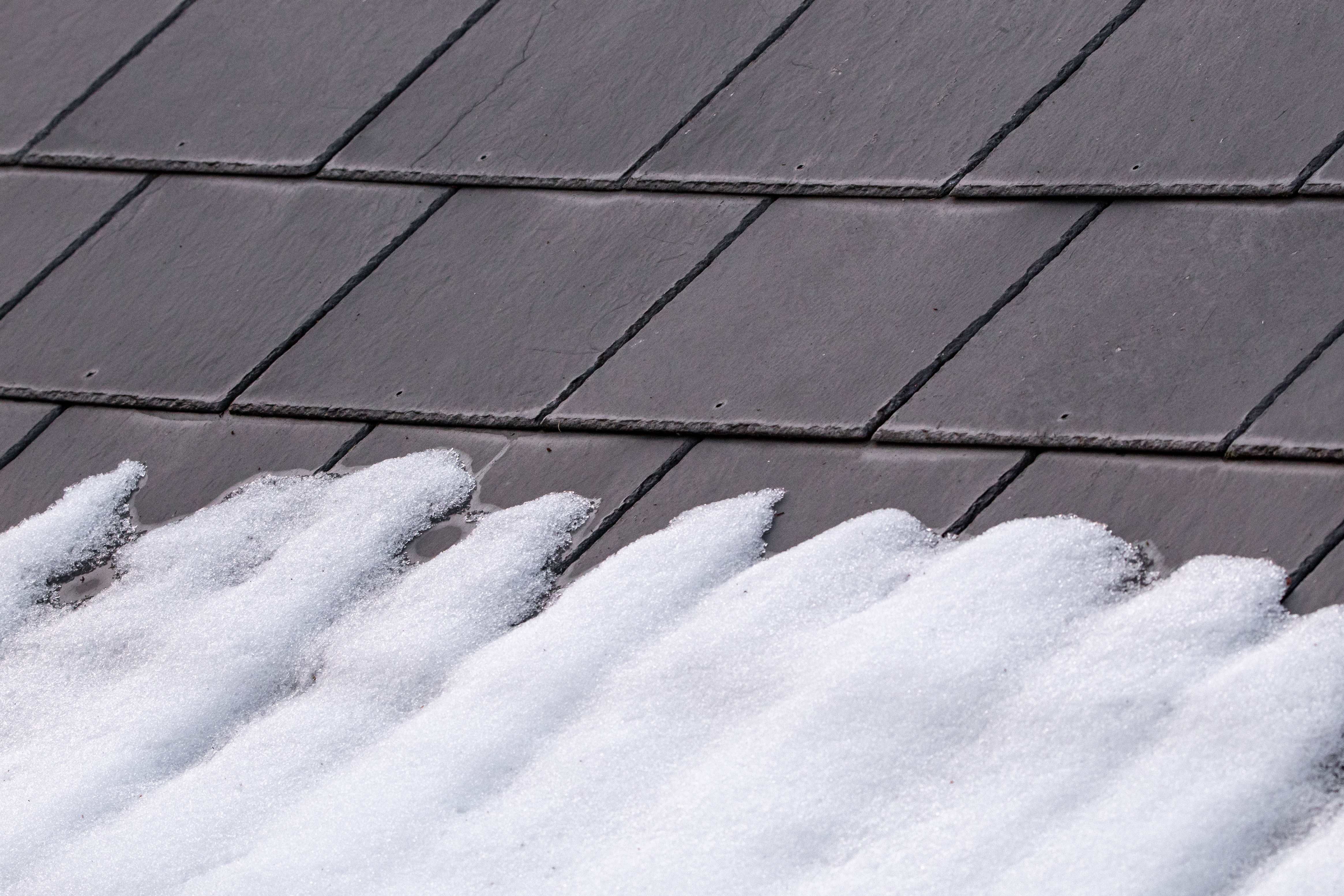 A Pattern of Grey Slates on a Roof with Melting Snow