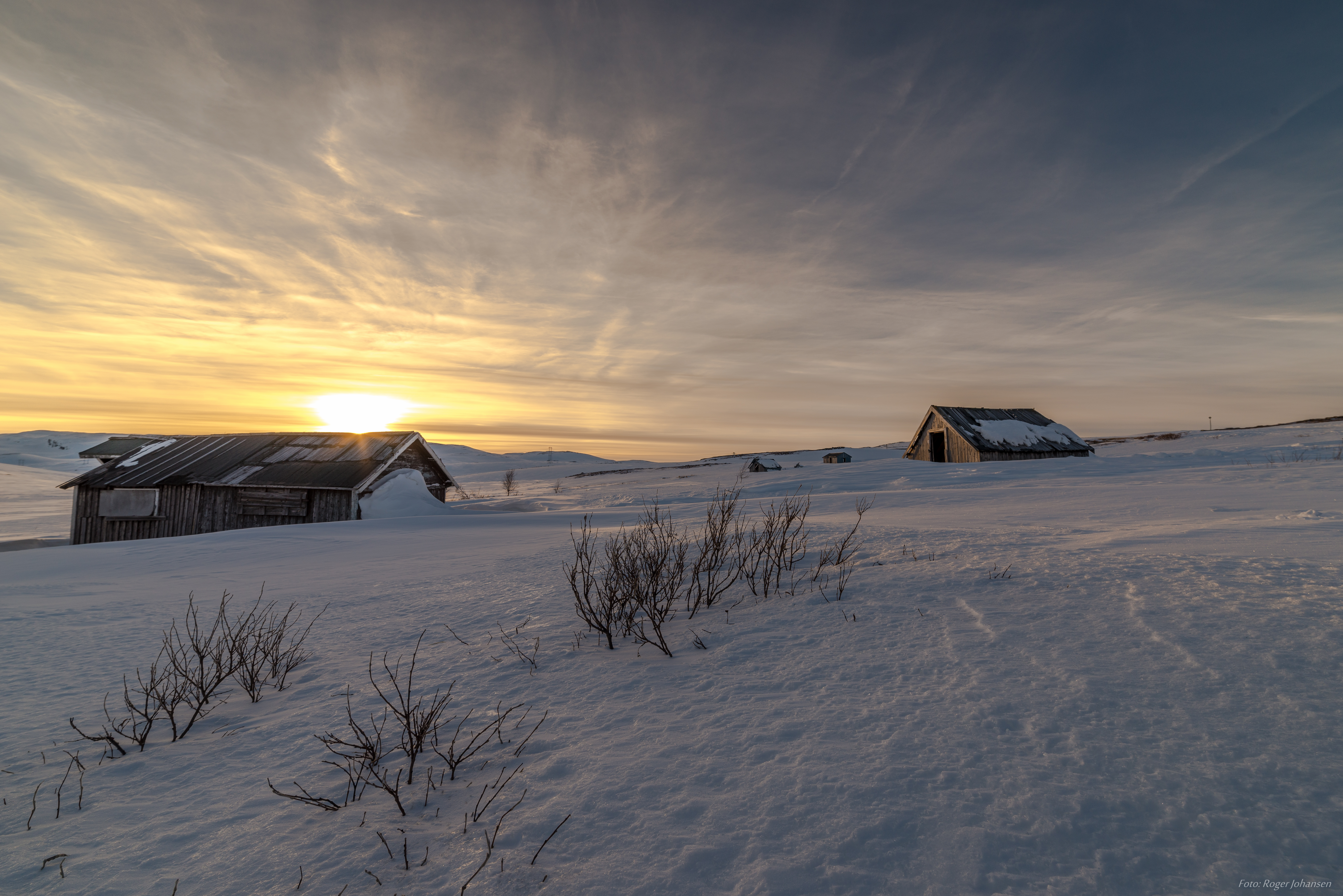 Sunset with old Sami cabins