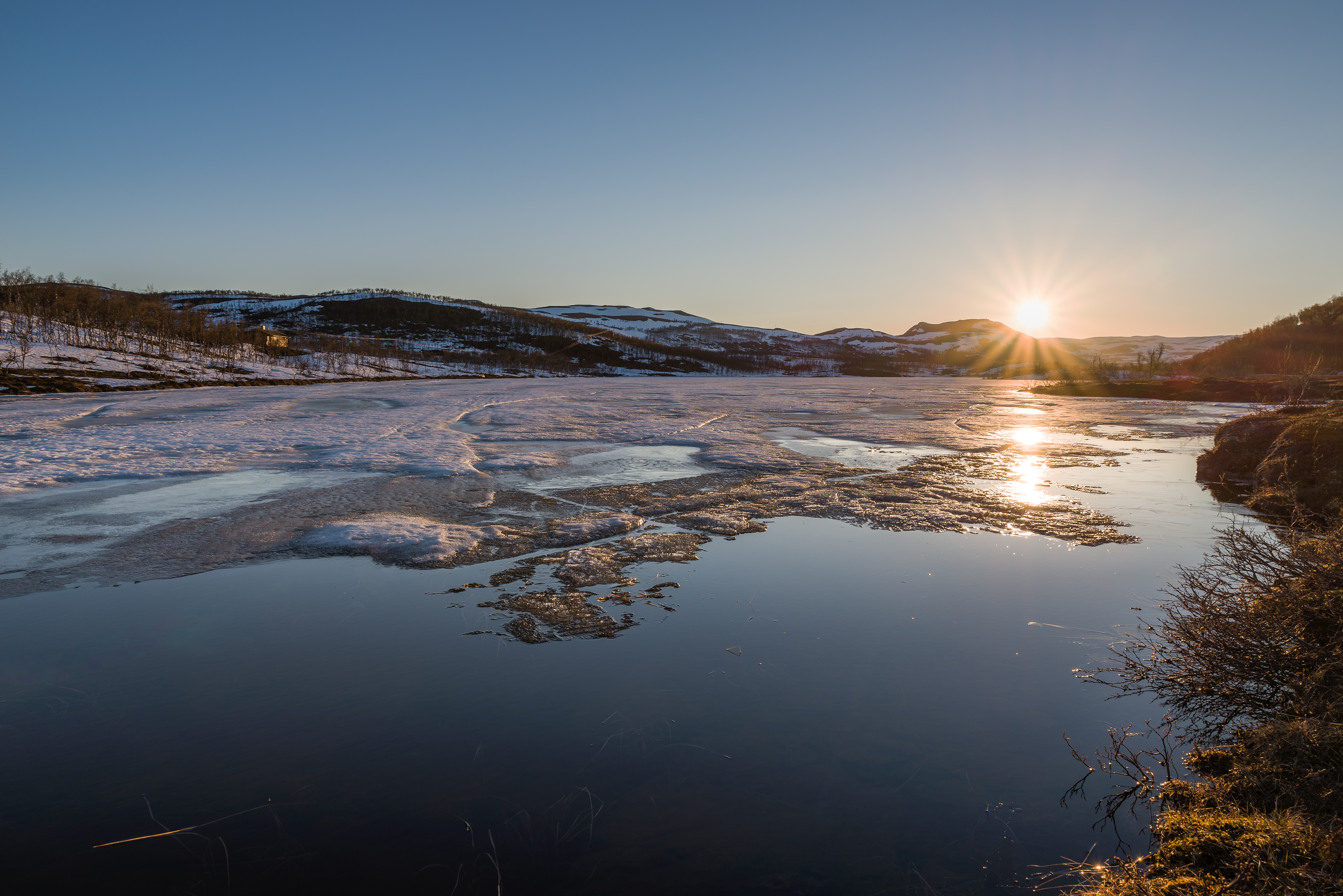 Midnightsun behind ice covered lake